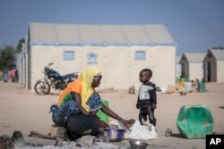 FILE - In this photo taken on Dec. 10, 2019 a displaced Burkinabe woman and child prepare food, in the Pissila town camp, near Kaya, Burkina Faso.