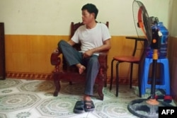 Pham Van Thin, father of 26-year-old Pham Thi Tra My, who is feared to be among the 39 people found dead in a truck in Britain, sits inside his house in Vietnam's Ha Tinh province, Oct. 26, 2019.