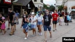 រូបឯកសារ៖ អ្នកទេសចរដែលពាក់ម៉ាស់ដើម្បីបង្ការជំងឺកូវីដ១៩ ដើរកំសាន្តនៅក្នុងរមណីយដ្ឋាន Walt Disney World ក្រុង Lake Buena Vista រដ្ឋ Florida ថ្ងៃទី១១ ខែកក្កដា ឆ្នាំ២០២០។