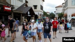 Para pengunjung pusat belanja Disney Springs di Lake Buena Vista, Florida, mengenakan masker wajah saat dibukanya kembali secara bertahap Walt Disney World setelah beberapa bulan tutup akibat pandemi Covid-19) AS 11 Juli 2020. REUTERS / Octavio Jones