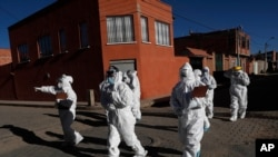 Dressed in full protective gear, doctors span out in a house-to-house new coronavirus testing campaign in the Villa Jaime Paz Zamora neighborhood of El Alto, Bolivia, July 4, 2020.