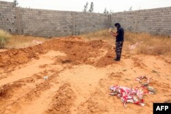 A member of security forces affiliated with the Libyan Government of National Accord's Interior Ministry stands at the reported site of a mass grave in Tarhuna, about 65 kilometers southeast of Tripoli, June 11, 2020.