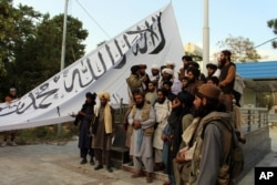 Taliban fighters pose for a photo while raising their flag at Ghazni provincial governor's house, in Ghazni, southeastern Afghanistan, Aug. 15, 2021.