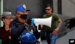 A police officer warns people to stay home as a precaution against the spread of the new coronavirus, in the historic center of Mexico City, April 1, 2020.