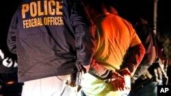 Trong bức ảnh ngày 22/10/2018, các nhân viên của cơ quan Thực thi Di trú và Hải quan Mỹ bắt giữ một người trong một cuộc bố ráp ở Richmond, Virginia. Cơ quan này được cho là sẽ bắt đầu các cuộc bố ráp di dân bất hợp pháp vào ngày 14/7.