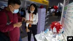 Seorang pengunjung mengenakan masker memperhatikan model virus corona untuk vaksin COVID-19 yang dipamerkan oleh perusahaan farmasi China Sinopharm di China International Fair for Trade in Services (CIFTIS) di Beijing, Sabtu, 5 September 2020.