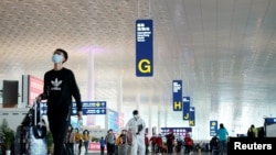 Travellers are seen at the Wuhan Tianhe International Airport after travel restrictions to leave Wuhan, the capital of Hubei province and China's epicentre of the novel coronavirus disease (COVID-19) outbreak, were lifted, April 8, 2020. REUTERS/Aly…