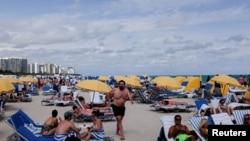 FILE - Revelers flock to the beach to celebrate spring break, amid the coronavirus outbreak in Miami Beach, Florida, March 6, 2021.