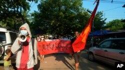 """Manifestantes marchan para protestar contra el golpe militar de febrero en Rangún, Myanmar, el domingo 11 de abril de 2021. La pancarta dice: """"Absolutamente no dictadura""""."""