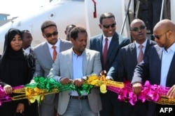 FILE - Abdirahman Omar Osman, center, and others celebrate after the first commercial flight by National Airways linking Addis Ababa to Mogadishu in 41 years landed in Mogadishu, Oct. 13, 2018. Mogadishu's mayor died Aug. 1.