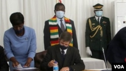 Andrew Pascoe (seated), the president of the Commercial Farmers Union of Zimbabwe, signs the agreement while President Emmerson Mnangagwa (with scarf) waits for his turn, at the State House in Zimbabwe, July 29, 2020. (Columbus Mavhunga/VOA)