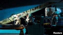 资料照片: 空军人员在德国斯潘达勒姆空军基地把货物装上一架支持美国非洲司令部特遣队的超级大力神运输机。 (2011年3月20日)