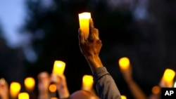 FILE - Marchers hold candles up as they listen to a speaker during a march and candlelight vigil for Ahmaud Arbery in the Satilla Shores neighborhood, in Brunswick, Ga., Feb. 23, 2021.