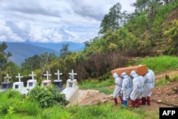 Health workers in protective suit carry a coffin with the body of a COVID-19 victim during a burial at a cemetery in Falam township in western Myanmar's Chin state, June 21, 2021. (Credit: Chinland Herald Daily News)