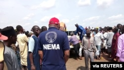 An official of the National Emergency Management Agency stands with a crowd gathered around a truck carrying bodies of the victims of a boat accident in Kebbi, Nigeria, May 27, 2021.