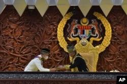 Sultan Abdullah Sultan Ahmad Shah, kanan, menerima dokumen dari Perdana Menteri Muhyiddin Yassin saat sidang parlemen di Kuala Lumpur, 18 Mei 2020. (Foto: AP)