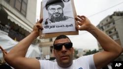 Pristalica Hezbolaha nosi sliku lidera pokreta Sajeda Hasana Nasralaha, tokom protesta u Bejrutu, 10. jula 2020. (Foto: AP)
