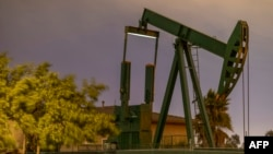 FILE - Pump jacks draw crude oil from the Long Beach Oil Field in Signal Hill, Calif., on March 9, 2020.