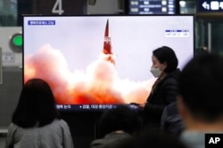 FILE - People watch a TV showing an image of North Korea's new guided missile during a news program at the Suseo Railway Station in Seoul, South Korea, March 26, 2021.