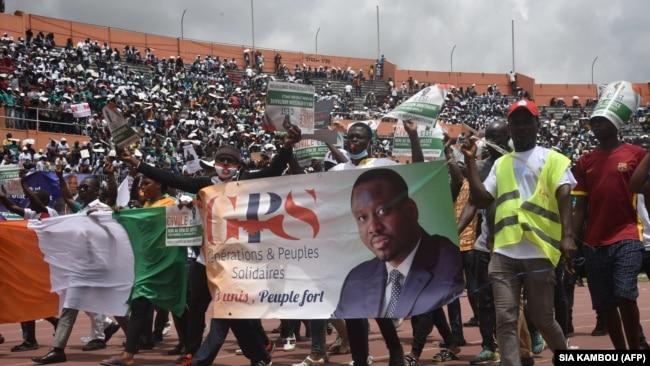 Des partisans du GPS, la formation politique de l'ancien Premier ministre Guillaume Soro, affichent un poster à son effigie au stade d'Abidjan, en Côte d'Ivoire, le 10 octobre 2020.