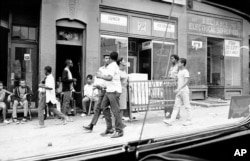 FILE - Two men carry furniture looted from a store in Newark, New Jersey, July 14, 1967.