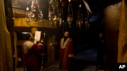 Christian Armenian pray inside the Grotto of the Church of the Nativity, traditionally believed by Christians to be the birthplace of Jesus Christ, in the West Bank city of Bethlehem on Christmas Eve, Tuesday, Dec. 24, 2019. (AP Photo/Majdi Mohammed)