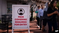 People without masks walk past a sign requesting customers to wear masks in Laguna Beach, Calif., May 17, 2021.