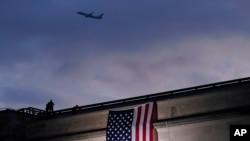 រូបឯកសារ៖ យន្តហោះហោះចេញពីអាកាសយានដ្ឋានជាតិ Washington Reagan ខណៈដែលទង់ជាតិអាមេរិកាំងធំមួយត្រូវបានដាក់បង្ហាញនៅឯមន្ទីរបញ្ចកោណមុននឹងប្រារព្ធពិធីគោរពវិញ្ញាណក្ខន្ធមនុស្ស១៨៤នាក់ដែលត្រូវបានសម្លាប់នៅក្នុងការវាយប្រហារភេរវកម្មថ្ងៃទី១១ ខែកញ្ញា ឆ្នាំ២០០១ នៅឯមន្ទីរបញ្ចកោណ។ (រូបថត AP)