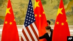 FILE - Chinese staffers adjust U.S. and Chinese flags before a session of negotiations between U.S. and Chinese trade representatives, at the Diaoyutai State Guesthouse, in Beijing, China, Feb. 14, 2019.