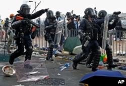 A policeman fires with a pepper ball gun towards protesters near the Legislative Council in Hong Kong, June 12, 2019.