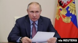 Russian President Vladimir Putin chairs a meeting with government members via a video conference call at Novo-Ogaryovo state residence outside Moscow, Russia, Feb. 10, 2021.