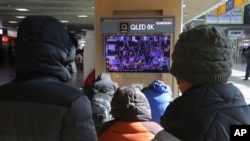 People watch a TV screen showing the news on a violent mob that loyal to U.S. President Donald Trump stormed the U.S. Capitol, at the Seoul Railway Station in Seoul, South Korea, Thursday, Jan. 7, 2021. (AP Photo/Ahn Young-joon)