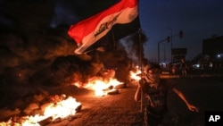 A protester runs holding an Iraqi flag as tires burn during a demonstration demanding better public services and jobs in Basra, southeast of Baghdad, Iraq, July 27, 2020.