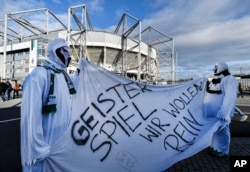 """Borussia fans dressed as ghosts hold a banner reading """"Ghost match - we want in"""" prior the German Bundesliga soccer match in Moenchengladbach, Germany, March 11, 2020. The match was played without spectators due to the coronavirus."""