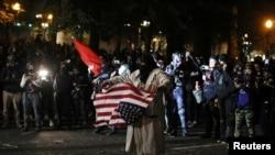 資料照片:在俄勒岡州的波特蘭市,一名示威者舉著美國國旗抗議警察暴力和種族不平等。 (2020年9月26日)