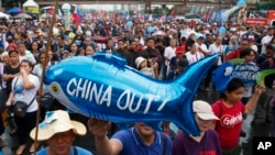 Protesters display a balloon with an anti-China message during a rally near the Philippine Congress to protest the 4th State of the Nation (SONA) address by President Rodrigo Duterte Monday, July 22, 2019 in suburban Quezon city, northeast of Manila.