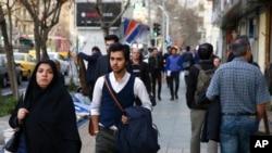 FILE - Amir Ali Najafi, center, a transgender man, walks on a sidewalk in Tehran, Iran, March 11, 2018. Transgender men and women can face harassment in Iran, despite a religious order acknowledging them.