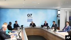 G-7 summit participants are seen during a session in Cornwall, England, June 12, 2021, with summit host, Britain's Prime Minister Boris Johnson, presiding.
