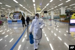 FILE - A State Commission of Quality Management staff member carries a disinfectant spray can as checks are done on the health of travelers at the Pyongyang Airport in Pyongyang, North Korea, Feb. 1, 2020.