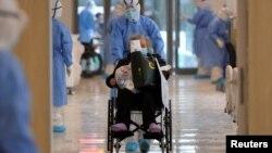 Seorang petugas mengenakan pakaian pelindung dan seorang pasien yang terinfeksi virus korona di sebuah rumah sakit di Wuhan, Provinsi Hubei, China, 10 Februari 2020. (Foto: China Daily via Reuters)