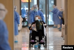 A medical worker in protective suit moves a novel coronavirus patient in a wheelchair at a hospital in Wuhan, Hubei province, China February 10, 2020. Picture taken February 10, 2020. China Daily via REUTERS ATTENTION EDITORS - THIS IMAGE WAS…