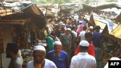 FILE - Rohingya refugees walk in the market area inside a refugee camp in Ukhia, Bangladesh, April 6, 2021.