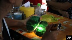 FILE - Local people examine the quality of a jade stone in the Hpakant area of Kachin state, northern Myanmar.