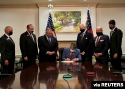 FILE - Georgia Governor Brian Kemp signs a voting law that activists said aims to curtail the influence of Black voters, in this handout photo posted to Kemp's Twitter feed on March 25, 2021.