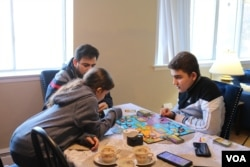 Syrian refugee Mohamed Almadani, 14, plays a game with younger sister Esraa, 10. He remembers gunfire and glass shattering in his home when the conflict in Syria escalated. (K. Khan/VOA)