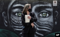 A woman wearing a face mask amid the spread of the new coronavirus walks past a mural of an Indigenous man in Bogota, Colombia, July 3, 2020.