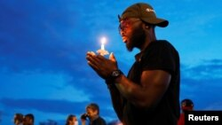 A man holds a candle as he reacts at the scene of the death, in Minneapolis police custody, of George Floyd in Minneapolis, Minnesota, June 3, 2020.