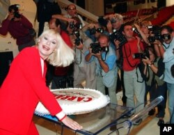 FILE - Raffaella Carra smiles as she poses for photographers during a press conference at Rome's Foro Italico, Sept. 30, 1999.