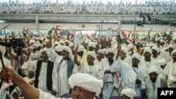 FILE - Supporters of Sudanese General Mohamed Hamdan Dagalo, also known as Himediti, deputy head of Sudan's ruling Transitional Military Council (TMC), raise up their sticks during a meeting with the General in the capital Khartoum, June 18, 2019.