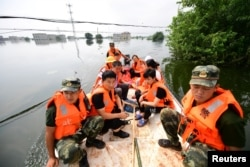 Paramilitary police officers evacuate residents from a flood-hit village with a boat in Yongxiu county of Jiujiang, Jiangxi province, China, July 14, 2020.